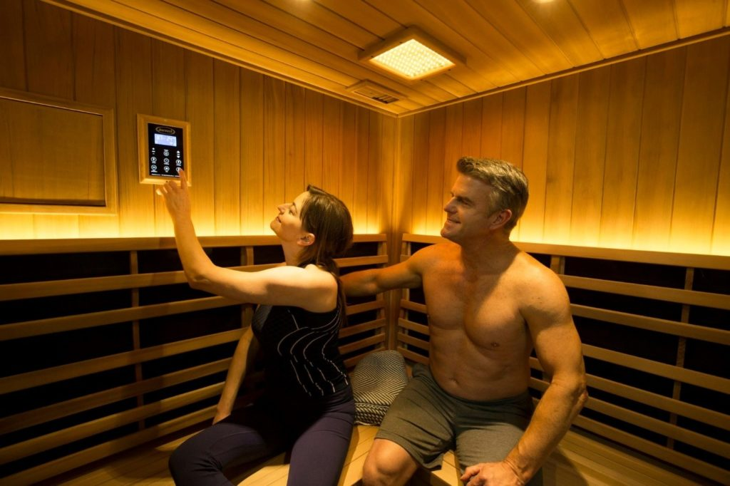 Man and woman adjusting temperature inside of a sauna