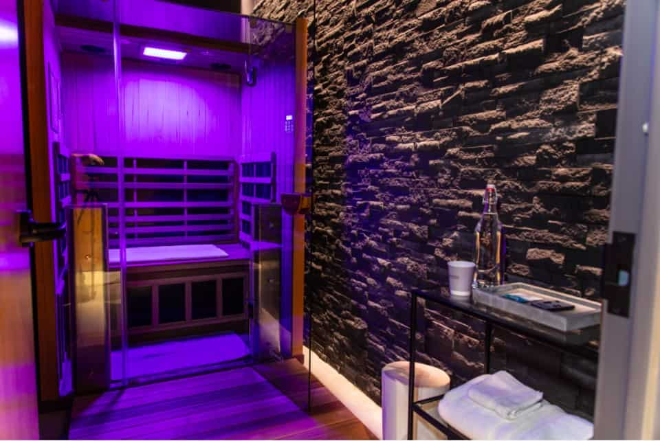 Illuminated Jacuzzi Infrared Sauna installed in a wellness room.